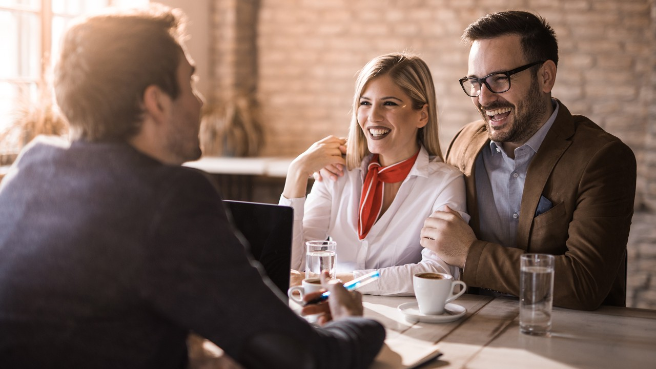 People talking with bank employee, smiling